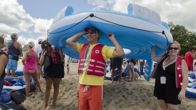 Harrison Plain, of Sarnia, waits to put his inflatable into the water Sunday, Aug. 21, 2016, at Lighthouse Beach in Port Huron.