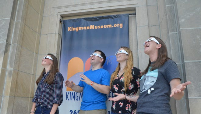 From left, Kingman Museum's Zoe Maddix, Josh Holderbaum, Etana Millard and Emily Powell demonstrate the safe way to look at a solar eclipse: through approved viewing glasses.