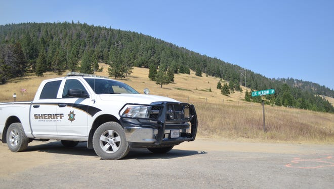 A Lewis and Clark County sheriff's deputy stands by near the Elk Meadows subdivision, where several residents have been evacuated. Ninety people in total have been evacuated due to the Alice Creek Fire.