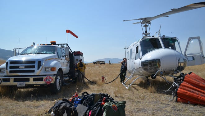Department of Natural Resource and Conservation crews refill helicopters next to Highway 200 near Highway 434 on Tuesday, Sept. 5.