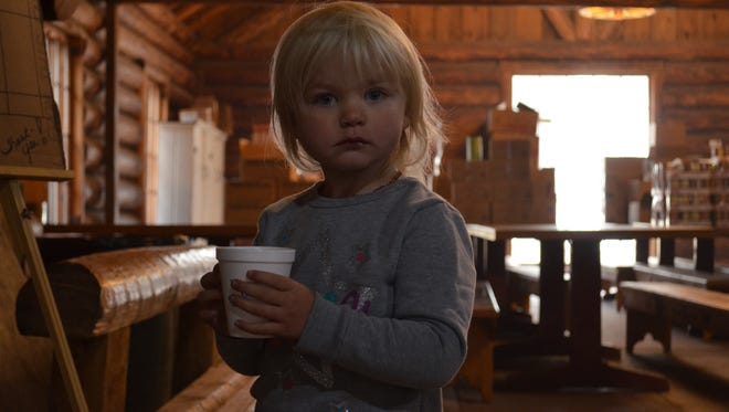 Remington Kittrell, 2, sips some juice at Camp Paxon, where her family has been staying since Seeley Lake residents were evacuated in late August. An area of town has since been reopened to residents.