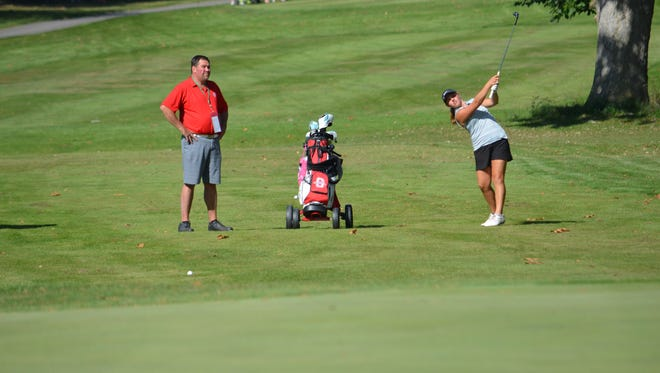 Shelby coach Brad Ruminski looks on as Lexi Uplinger hits an approach shot during Monday's Division II district golf tournament.