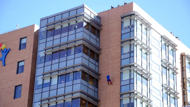In this Tuesday, Oct. 17, 2017, photo, officers from the Aurora police department repelled in costume from the roof of Children's Hospital Colorado as part of SWAT training in Aurora, Colo. Some officers repelled upside down, waving at children through windows as they repelled.  The hospital treats hundreds of children from all over the country that need specialized care. Children are treated for many different illnesses at the facility, ranging from eating disorders, heart surgery, dermatological care, cancer, and more. (AP Photo/Tatiana Flowers)