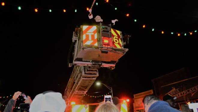 At the end of the annual Main Street Vineland Christmas parade, Santa was lifted up in a Vineland Fire Department truck to light the red and green Christmas lights that line Landis Avenue.