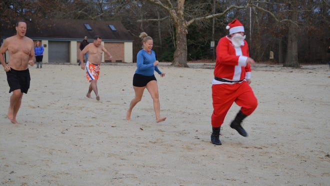 Swimmers follow Santa into Parvin Lake for the annual Parvin Polar Plunge on Saturday, Dec. 2. Photo/Jodi Streahle