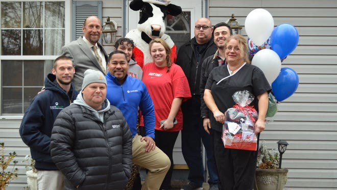 Jodi Algeri of Egg Harbor Township is the winner of the 10th Annual East Coast Roofing, Siding & Windows roof giveaway. She is pictured with her three children, Angelo, Marla and Gina, and representatives from participating businesses moments after the surprise announcement. East Coast Roofing, Siding & Windows will replace the roof; Apex Gutters will donate gutters; Universal Supply Company will provide materials and Clean Lines Painting & Power Washing will complete interior work. Chick-Fil-A of Egg Harbor Township provided lunch during the presentation. Photo/Jodi Streahle