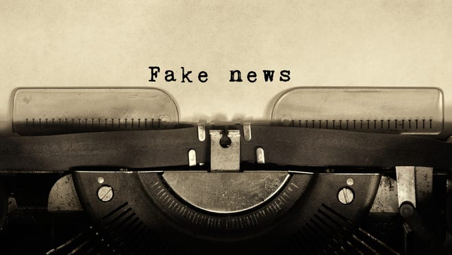 """Vintage typewriter with sheet of paper and words """"fake news."""""""