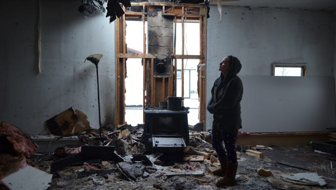 Heather Amelsberg returns to her home to collect some toys for her seven children after a house fire ripped through much of their home on Dec. 26.