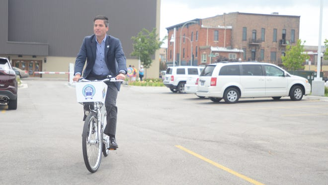City Manager James Freed takes the first official ride on a rental bicycle around the parking lot of Blue Water Transit's bus hub on Wednesday, July 12, 2017, as part of Port Huron's new bike-sharing program.