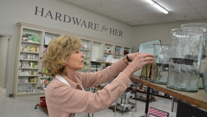 Lisa Rooks fills shelves with merchandise in the Hardware For Her section of Revell Ace Hardware in Deville Plaza. Hardware for Her includes cookware, cutlery and other kitchen products and housewares.