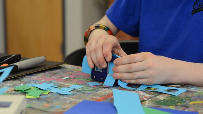 Keegan Nace cuts out blue and green shapes for a mosaic project at Art Inspired Academy.