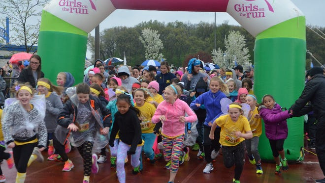 Runners take off for the start of the 2018 Calhoun County Girls on the Run 5K at Harper Creek High School on Friday, May 11.