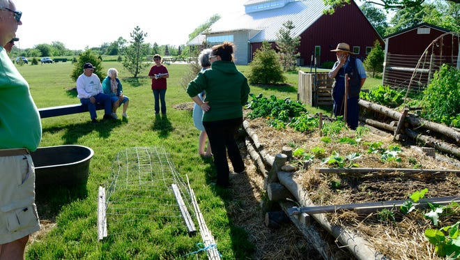 Aly Rumer, naturalist and volunteer coordinator with Sandusky County Park District, teaches how to grow a raised bed or a container garden at Wilson Nature Center at Creek Bend Farm on Monday evening.