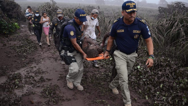 Police officers carry a wounded man after the eruption of the Fuego Volcano, in El Rodeo village, Escuintla department, south of Guatemala City on Monday.