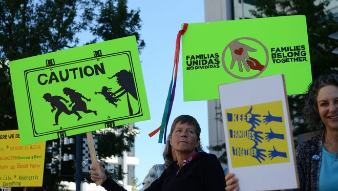 Protesters lined South Virginia Street in front of the Bruce R. Thompson Federal Building on Tuesday, calling for lawmakers to take action on family separation at the U.S. border.