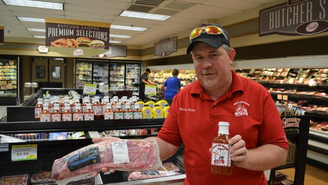 Owner Kim Lemke with Kim's BS BBQ Sauce and ribs at the Trig's grocery store location in Weston, one of around 200 retail locations across Wisconsin where his BBQ sauce is sold.