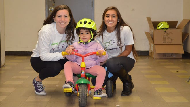 Bridget Salice (left) and Cristiana Villani (right ), both of Rye and with Linking Handlebars, get a young girl rolling on her bicycle.