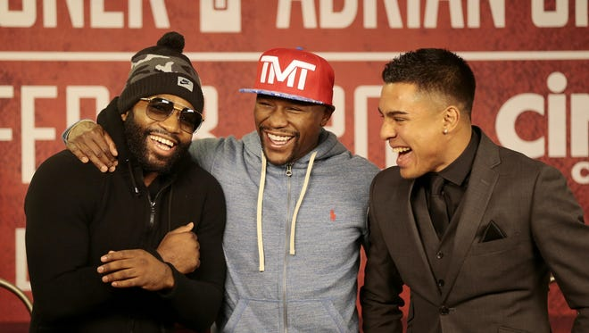 Fighters Adrien Broner (left) and Adrian Granados (right) laugh with retired champion Floyd Mayweather after they faced off during a press conference in January to promote the upcoming fight between Broner and Granados.