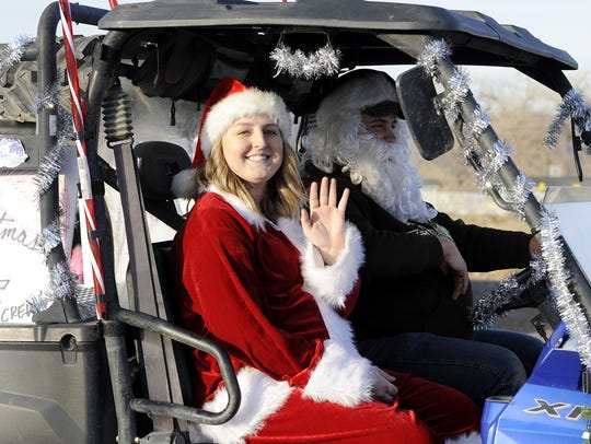 Kelsey and Jake Kibbe wave from an off-road vehicle.
