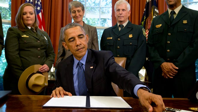 President Barack Obama, signs designations for three new national monuments; Berryessa Snow Mountain in California, Waco Mammoth in Texas, and the Basin and Range in Nevada, in the Oval Office of the White House Friday, July 10, 2015, in Washington. Behind him from left are April Slayton, chief of public affairs and  chief spokesperson of the National Park Service; Secretary of the Interior Sally Jewell; U.S. Forest Service Chief Tom Tidwell; and Randy Moore, Forest Service.