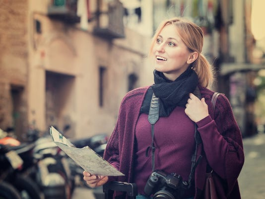 Traveling girl searching for direction using paper map