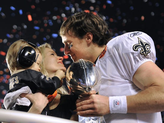 New Orleans Saints quarterback Drew Brees celebrate the win with his son Baylen and wife Brittany on the podium air after beating the Colts 31-17 in Super Bowl XLIV Sunday, February 7, 2010 in Miami.