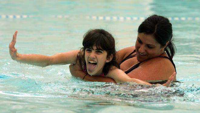 Therapy aide Allison Caiazza of Freehold Township works with Schroth School student Nicole Hogan, 18, of Neptune in the pool at  Camp Oakhurst in 2009.