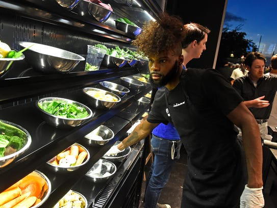 Torion Cross reaches for fresh fruits and veggies to