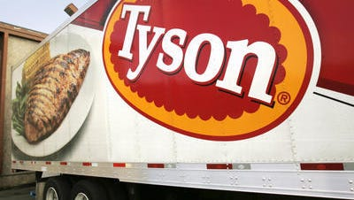 A Tyson Foods Inc., truck is parked at a food warehouse in Little Rock, Ark. Tyson Foods plans to sell its poultry businesses in Mexico and Brazil for $575 million in cash to help pay debt from its recently announced acquisition of Hillshire Brands.