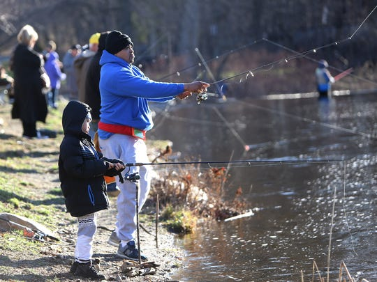 7-year-old Gabe Torres and David Holmes of Dover join other anglers on the first day of New Jersey trout fishing in the Rockaway River. April 8, 2017, Rockaway, NJ