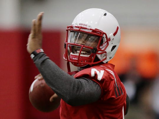 FILE - In this March 8, 2014 file photo, Nebraska quarterback Tommy Armstrong Jr.  smiles while throwing on the first day of NCAA college spring football practice in Lincoln, Neb. Armstrong was 7-1 as a starter last year but he threw eight interceptions. He threw one interception for every 16.3 pass attempts, one of the worst marks in the country. (AP Photo/Nati Harnik, File)