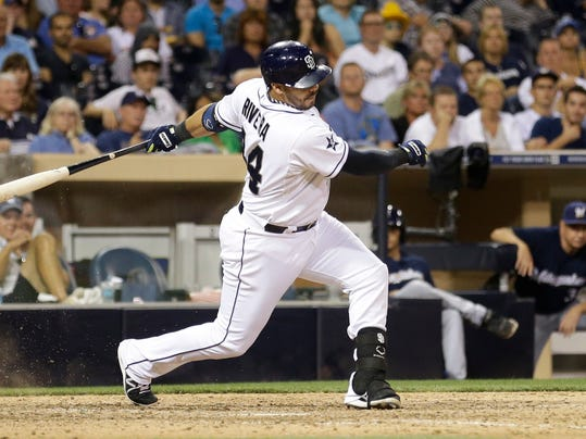 San Diego Padres' Rene Rivera follows through on an RBI single to beat the Milwaukee Brewers during the 10th inning in a baseball game Wednesday, Aug. 27, 2014, in San Diego. The Padres won 3-2. (AP Photo/Gregory Bull)