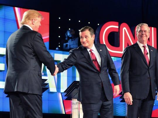 Ted Cruz reaches over to shake Donald Trump's hand