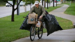 Laden with aluminum cans, Gary Gates rides his bike