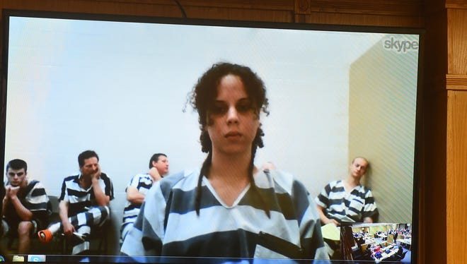 Monique Blanc is shown on a video screen during her arraignment today in Baxter County Circuit Court