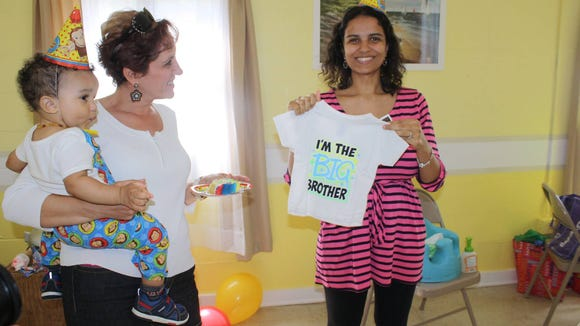 Sila hold up the shirt announcing she is pregnant. She is due Dec. 1.