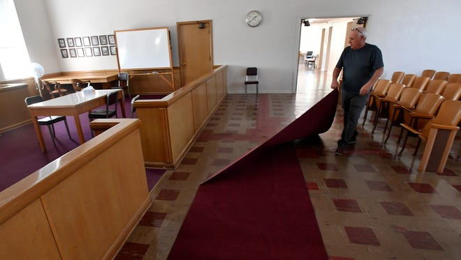 Coleman County Judge Billy Bledsoe pulls back a rug to expose a patched crack in the second floor courtroom of the county courthouse. The county will receiver a more than $130,000 grant from the Texas Historical Commission to repair the foundation in the 134 year-old courthouse.