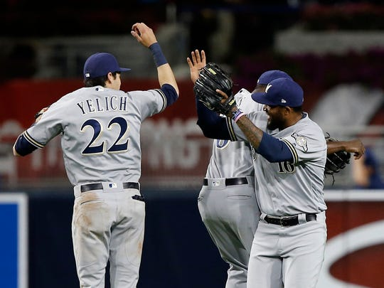 Brewers outfielders Christian Yelich (left) Lorenzo Cain and Domingo Santana celebrate their victory over the Padres last week in San Diego.