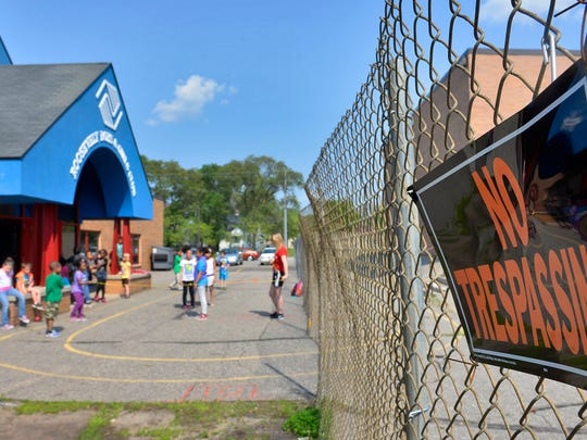 """A bent """"no trespassing"""" sign hangs on a cyclone fence that bisects the paved part of the playground between the old Roosevelt school and the Roosevelt Boys & Girls Club on May 27 in St. Cloud. Since the fire last year that destroyed the adjacent Roosevelt school, part of the playground remains unusable because of the construction around the school."""