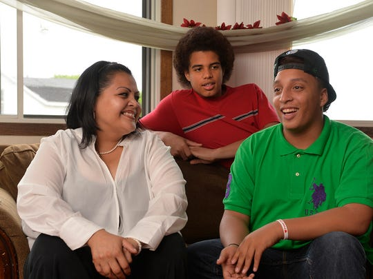 Erica Johnson listens as her boys, James, 17, right, and Jesus, 14, talk June 3 at their St. Cloud apartment about the things they loved about the Roosevelt Boys & Girls Club, including the gym they used before the fire at Roosevelt Education Center last year.