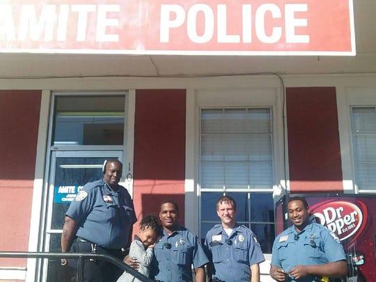 Rosalyn Baldwin, 7, of Hammond, hugs an officer with