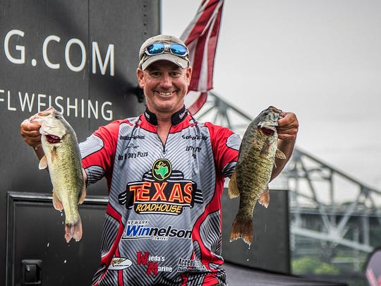 Ron Nutter of Newark shows off a pair of the bass he caught during the FLW TH-Marine All-American Bass Tournament in Alabama's Pickwick Lake.