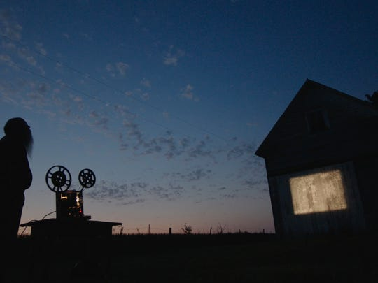 Michael Zahs with the projection of the old Brinton films on his rural Washington shed.