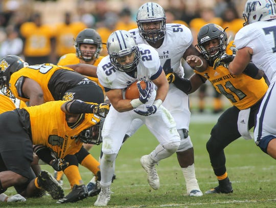 Monmouth back Peter Guerriero cuts through a hole in
