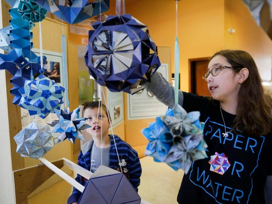 Katherine Adams shows Henry Bongers of Oshkosh different types of origami during a workshop at the Paper Discovery Center in Appleton on, Saturday, Oct. 17. Katherine and her sister, Isabelle, started Paper For Water, a nonprofit that through donations to purchase origami ornaments helps provide wells for clean water.