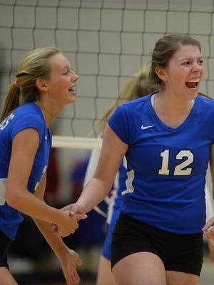 Centerville's Elaina McClanahan, left, and Sarah Stelle celebrate a point during a sectional volleyball match against Lincoln at Knightstown, Thursday, Oct. 23, 2014.