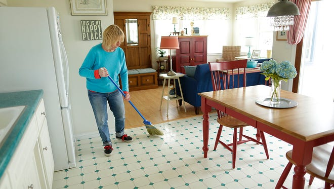 Shirley Maloney sweeps her kitchen floor inside her waterfront beach house in the Town of Scott on Wednesday. Maloney is in the process of selling her home.