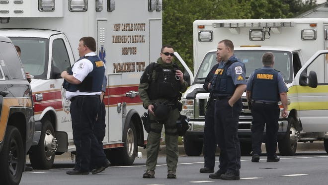 Emergency personnel standby on Brick Mill Road as a man suspected of shooting a state police officer is involved in a police standoff at his home in Brick Mill Farm Wednesday afternoon.