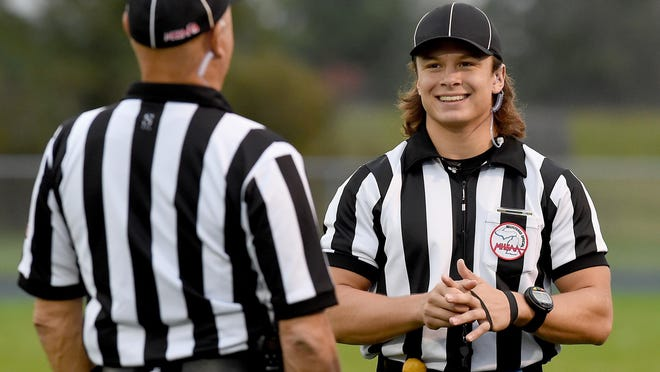 Bryant Moore, 19, of Sand Creek talks with referee Bill Gomoluch before the Hillsdale at Ida varsity football game.