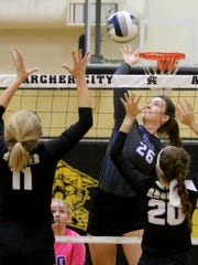 Windthorst's Mollee Kirk spikes the ball past Archer City's Lauren Castles (11) and Abby Aulds (20) Saturday, Sept. 30, 2017, in Archer City. The Trojanettes won in three sets, 25-22, 25-15, 25-14.